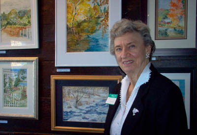 "Marilyn Patterson of Sudbury stands next to her painting entitled ""Icy Stream"" (lower right)"