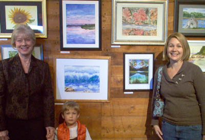 "Pat Selin of Stow (left) stands next to her grandson Dylan York and her daughter Meredith York of Ipswich in front of Pat's painting entitled ""Dance of the Sea"""